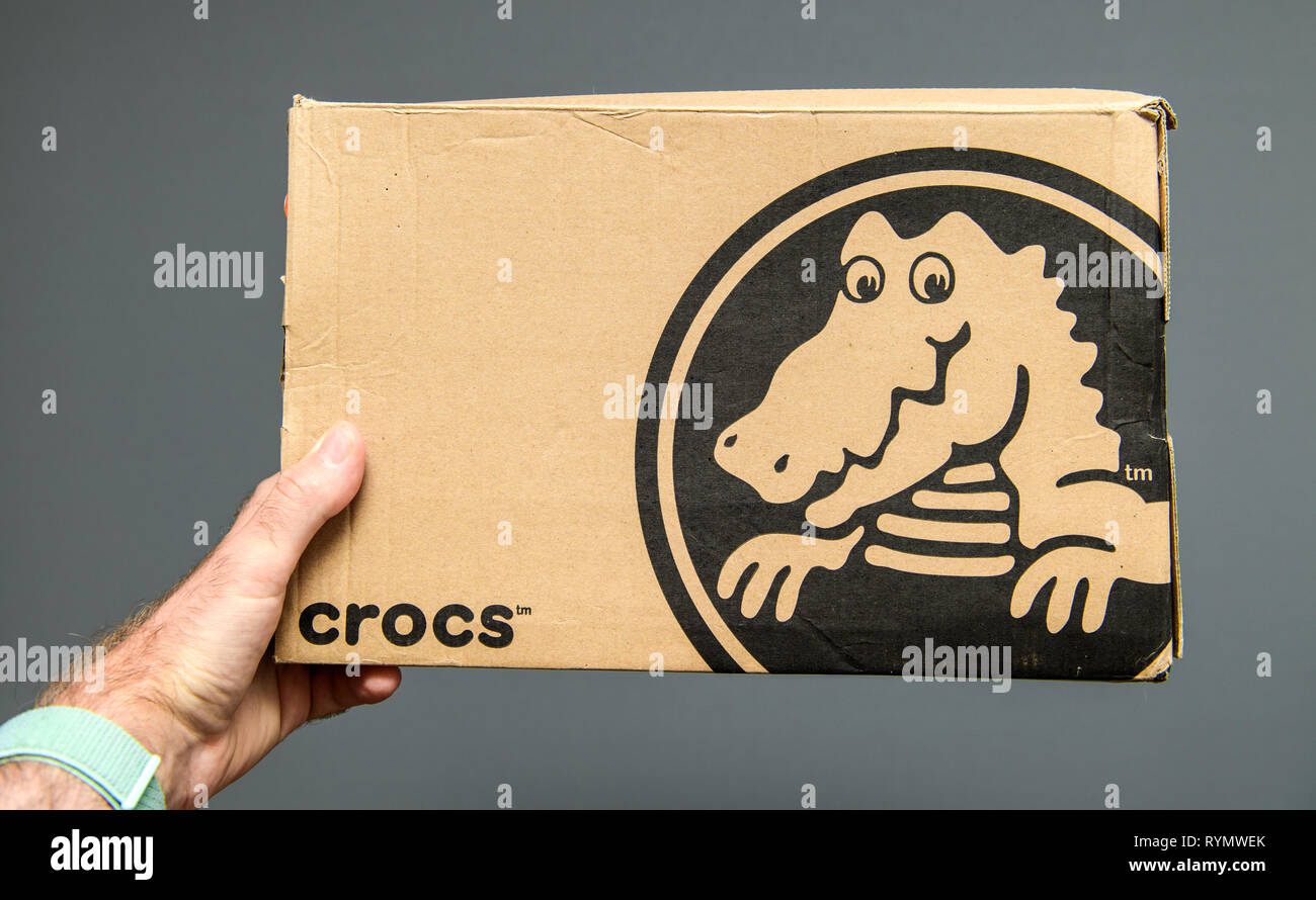 Paris, France - Jun 12, 2018: Man hand holding Freshly delivered Crocs shoes cardboard box featuring big crocodile logotype gray background - Stock Image