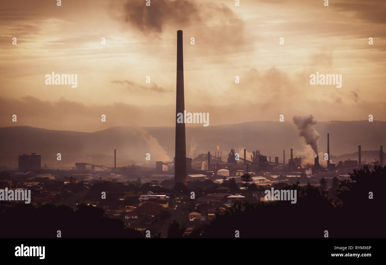 High view across industrial town to steel works and smoke stacks on atmospheric evening. Old industries, climate change and global warming concept - Stock Image