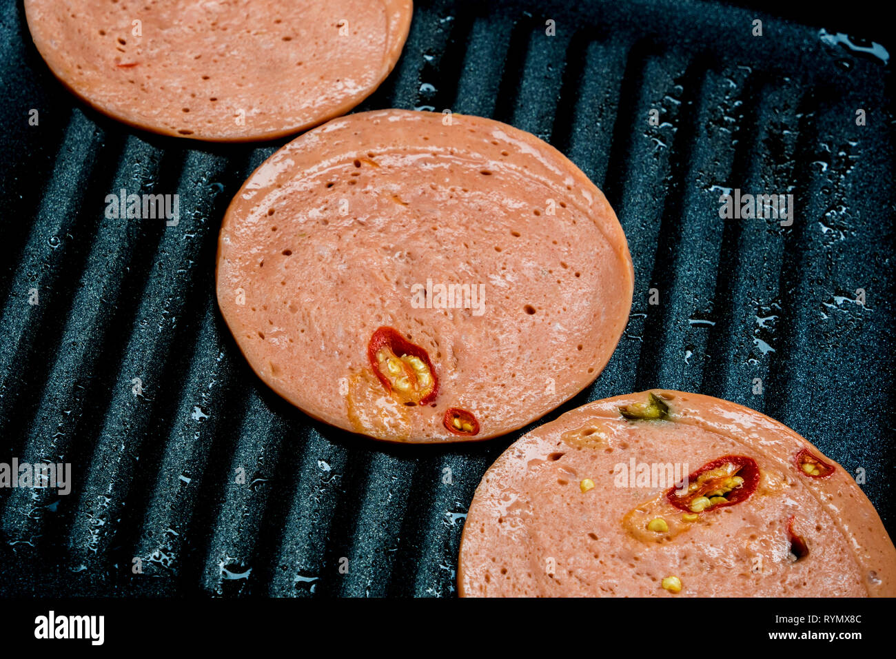 Spices Bologna fried in cooking pan - Stock Image