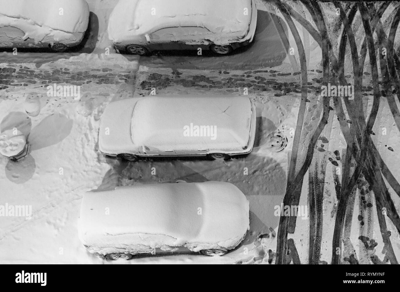 Parked cars and footprints in the snow in black and white style top view - Stock Image