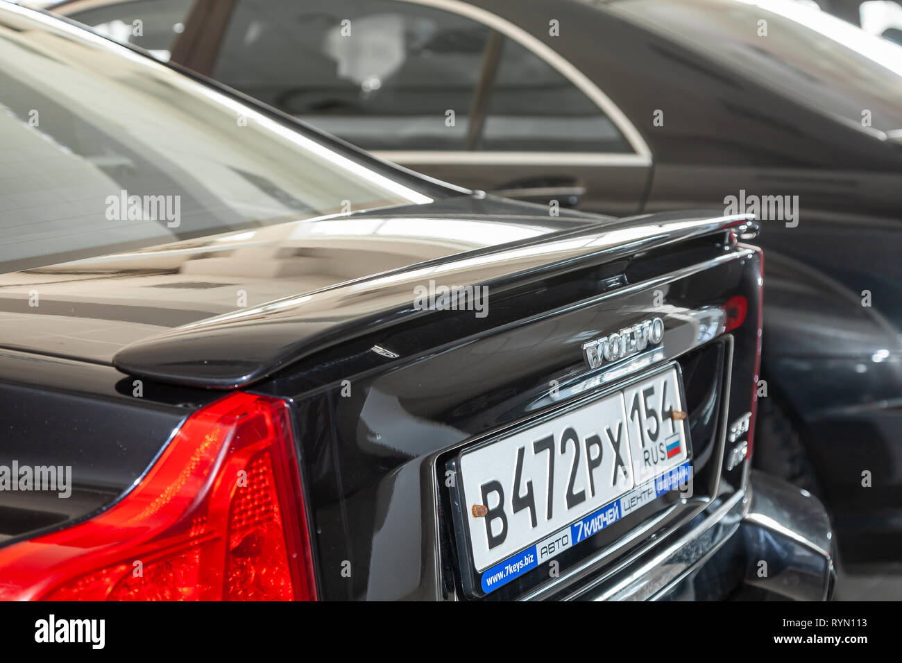 Novosibirsk, Russia - 08.01.18: Rear spoiler on the trunk of black used Volvo S60 car stands in the auto sale after wadhing - Stock Image