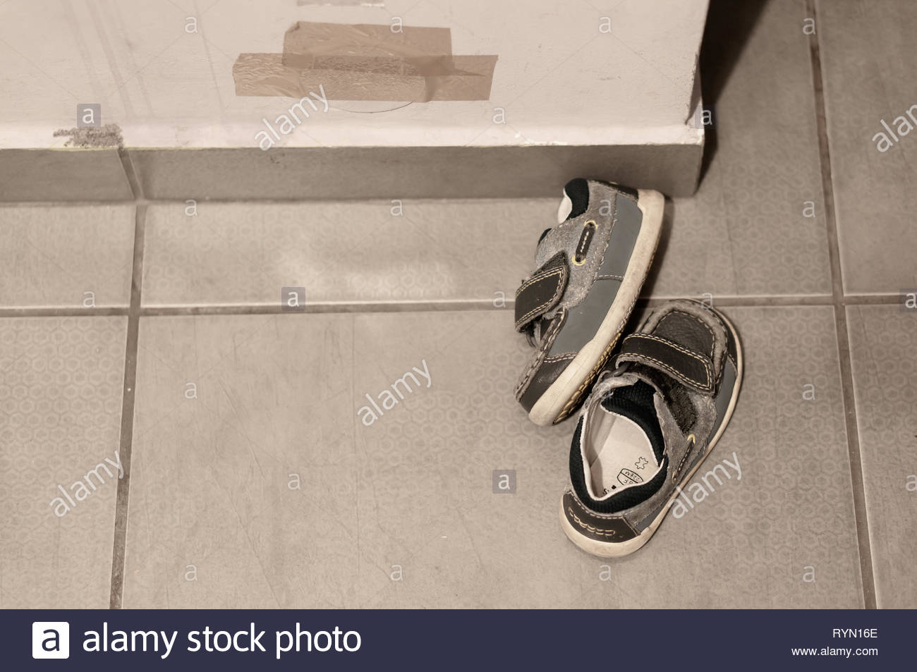 Poznan, Poland - March 8, 2019: Pair of small leather child shoes laying on a tile floor next to a wall. Stock Photo