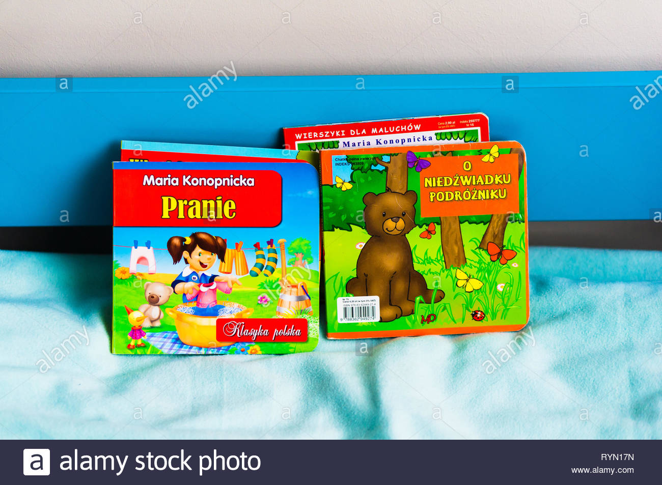 Poznan, Poland - November 18, 2018: Colorful Polish books on a blue bed with soft sheet. Stock Photo