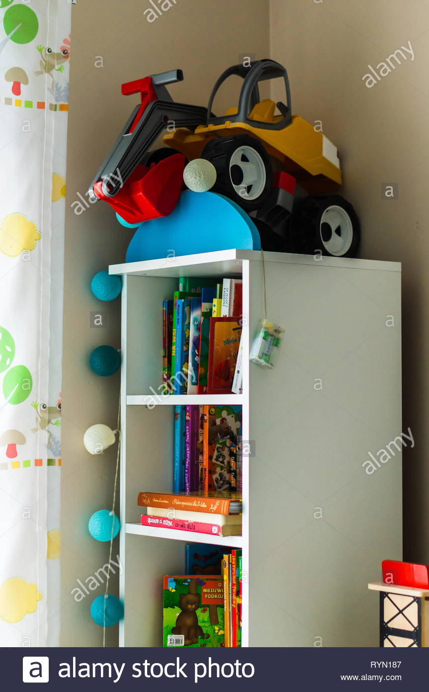 Poznan, Poland - November 18, 2018: White bookshelf with plastic toy excavator on the top in a child room. Stock Photo