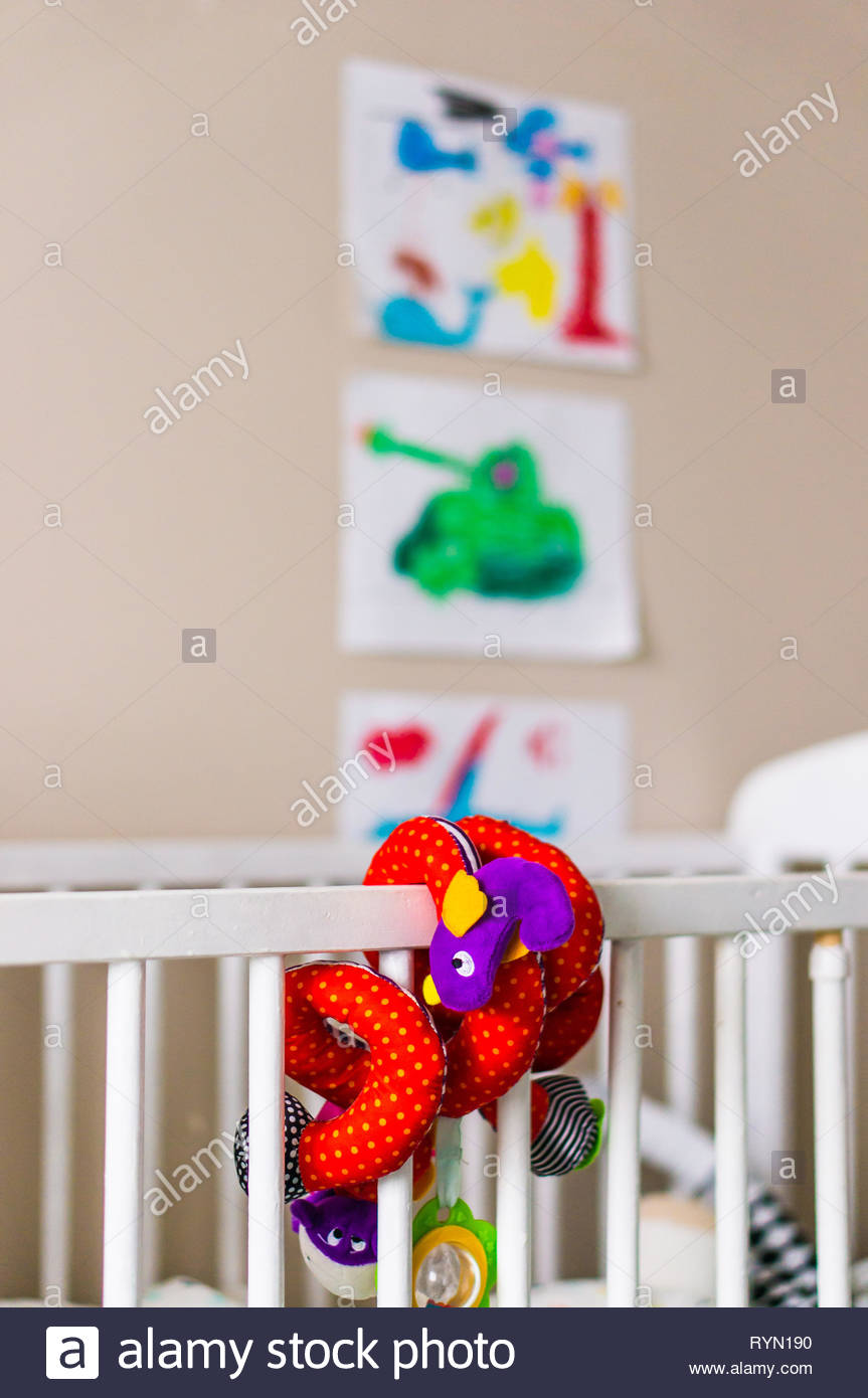 Poznan, Poland - November 18, 2018: Colorful toy snake attached on a wooden baby bed in a child room. Stock Photo