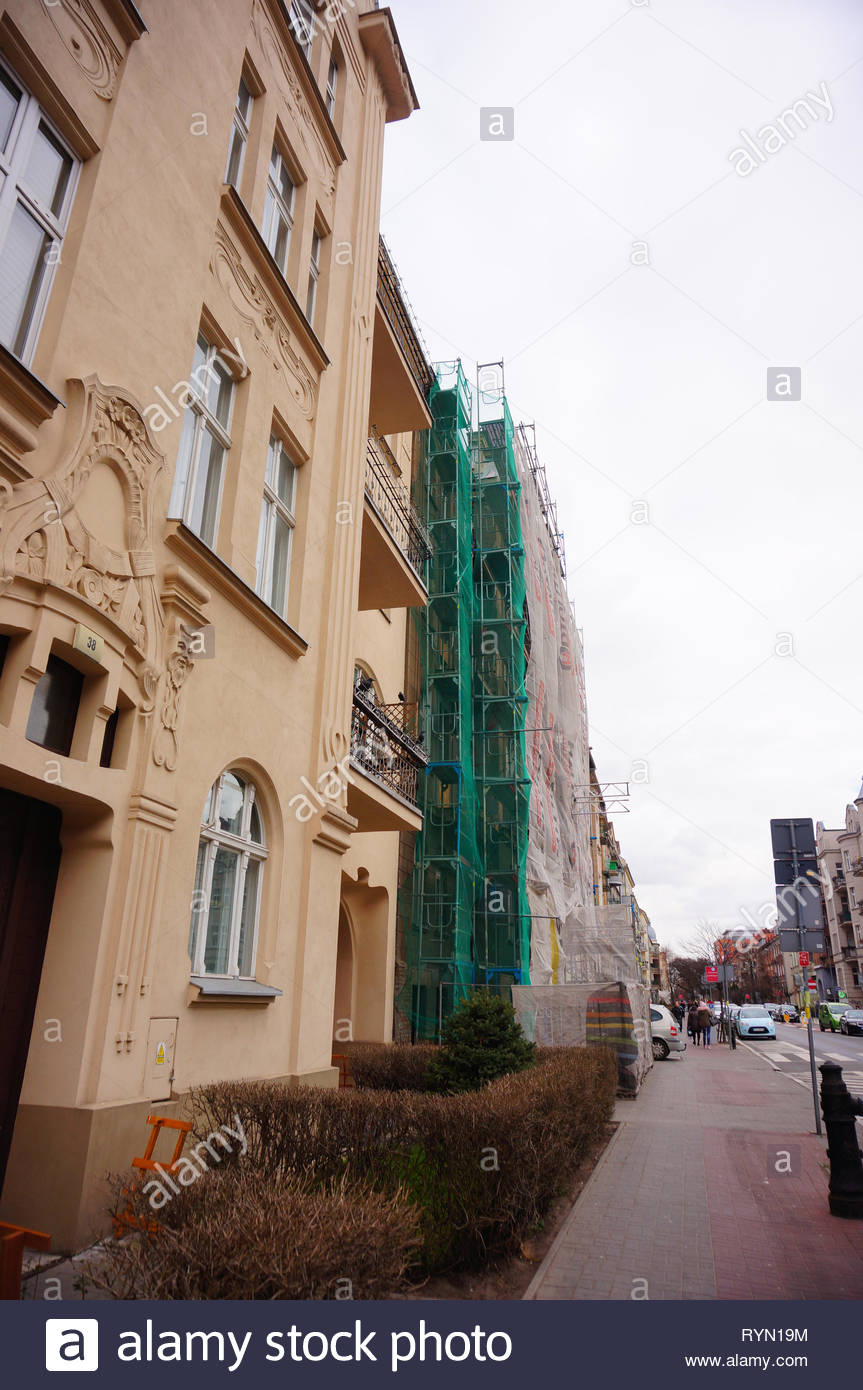Poznan, Poland - March 8, 2019: Building under construction by a sidewalk on the Slowackiego street in the city center on a cloudy day. Stock Photo
