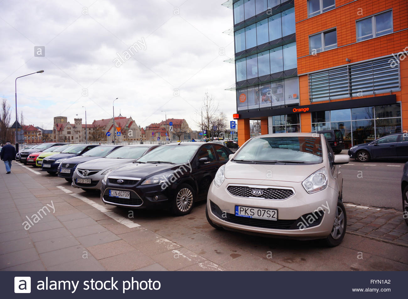 Poznan, Poland - March 8, 2019: Row of parked cars on parking spots close by the Globis office building with Orange telecommunication shop on the Slow Stock Photo