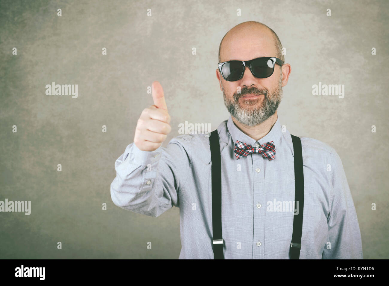 happy man with sunglasses and bow tie showing thumbs up against gray background - Stock Image