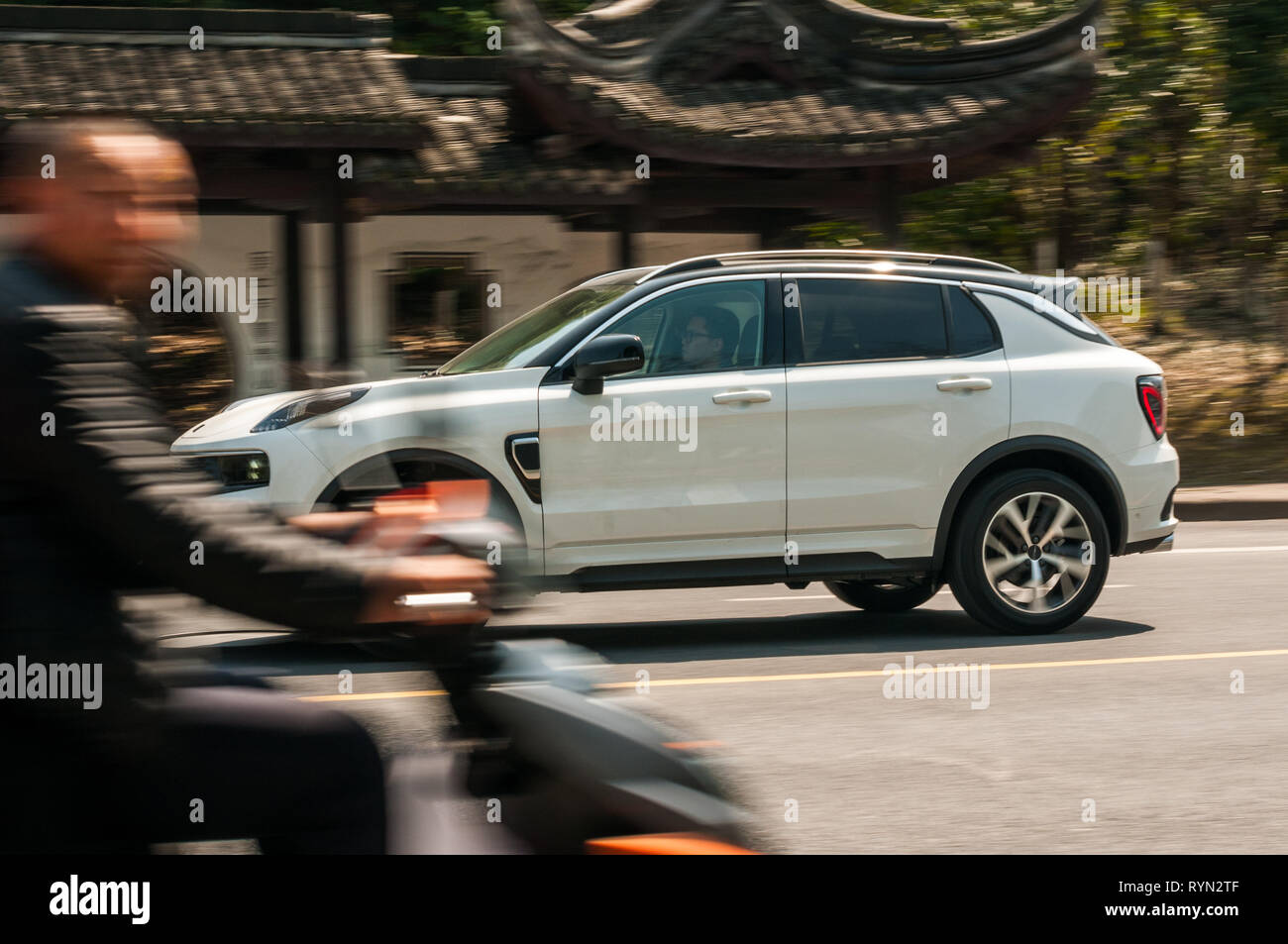 A young man drives past in a Chinese made electric SUV as a man on an electric scooter goes in the other direction. In the background is a bus stop ma - Stock Image