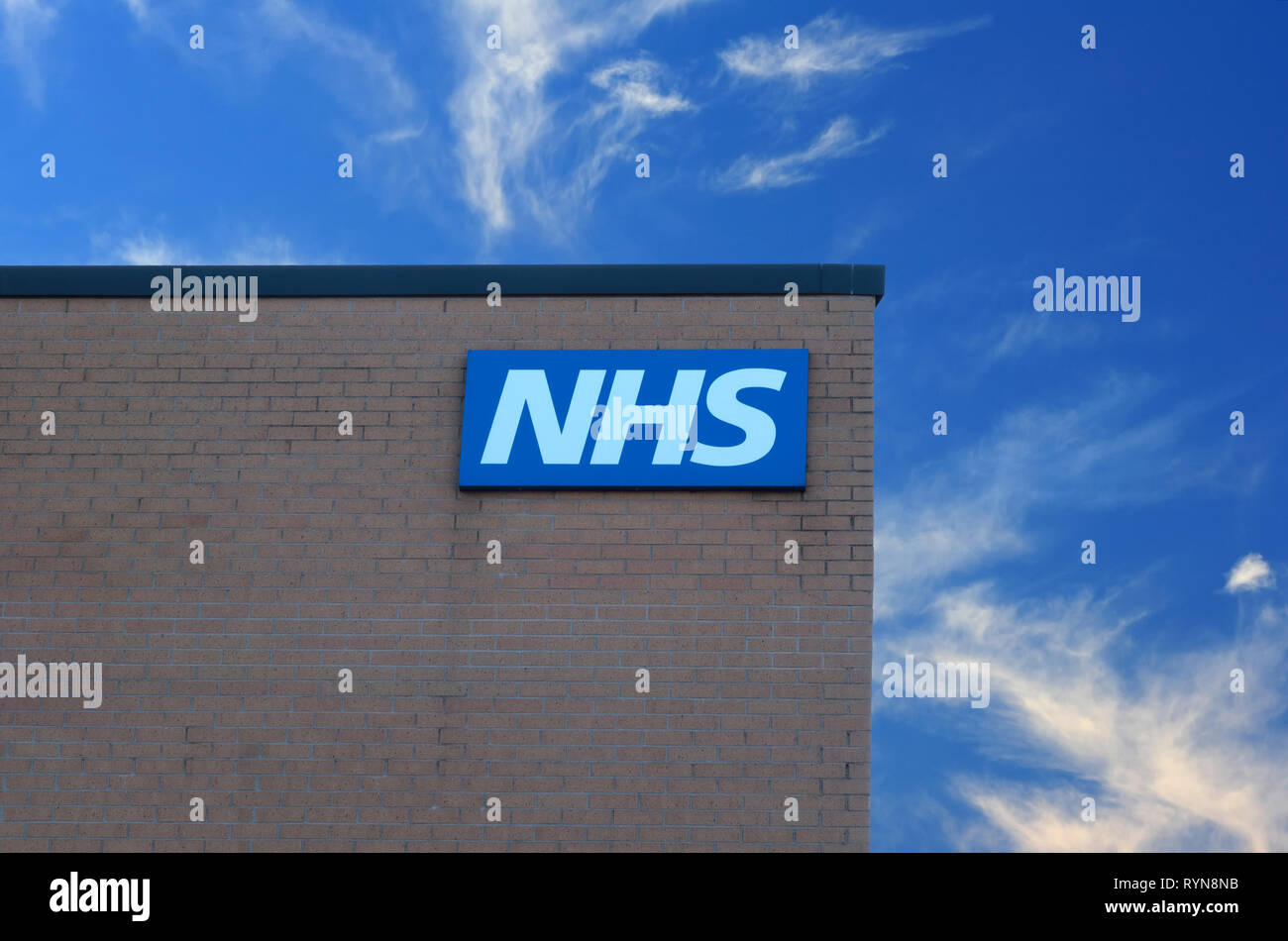 NHS sign on the outside wall of a  UK health centre building against a blue sky. - Stock Image