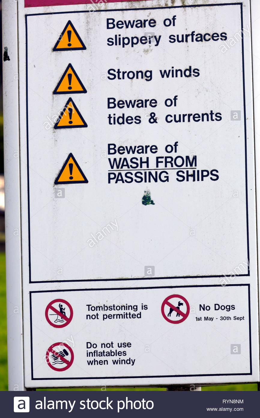 warning sign,beware of wash from, ships,strong,winds,slippery,surfaces,tides, currents,passing,tombstoing,not, permitted,no,dogs, Gurnard, Isle of Wig - Stock Image