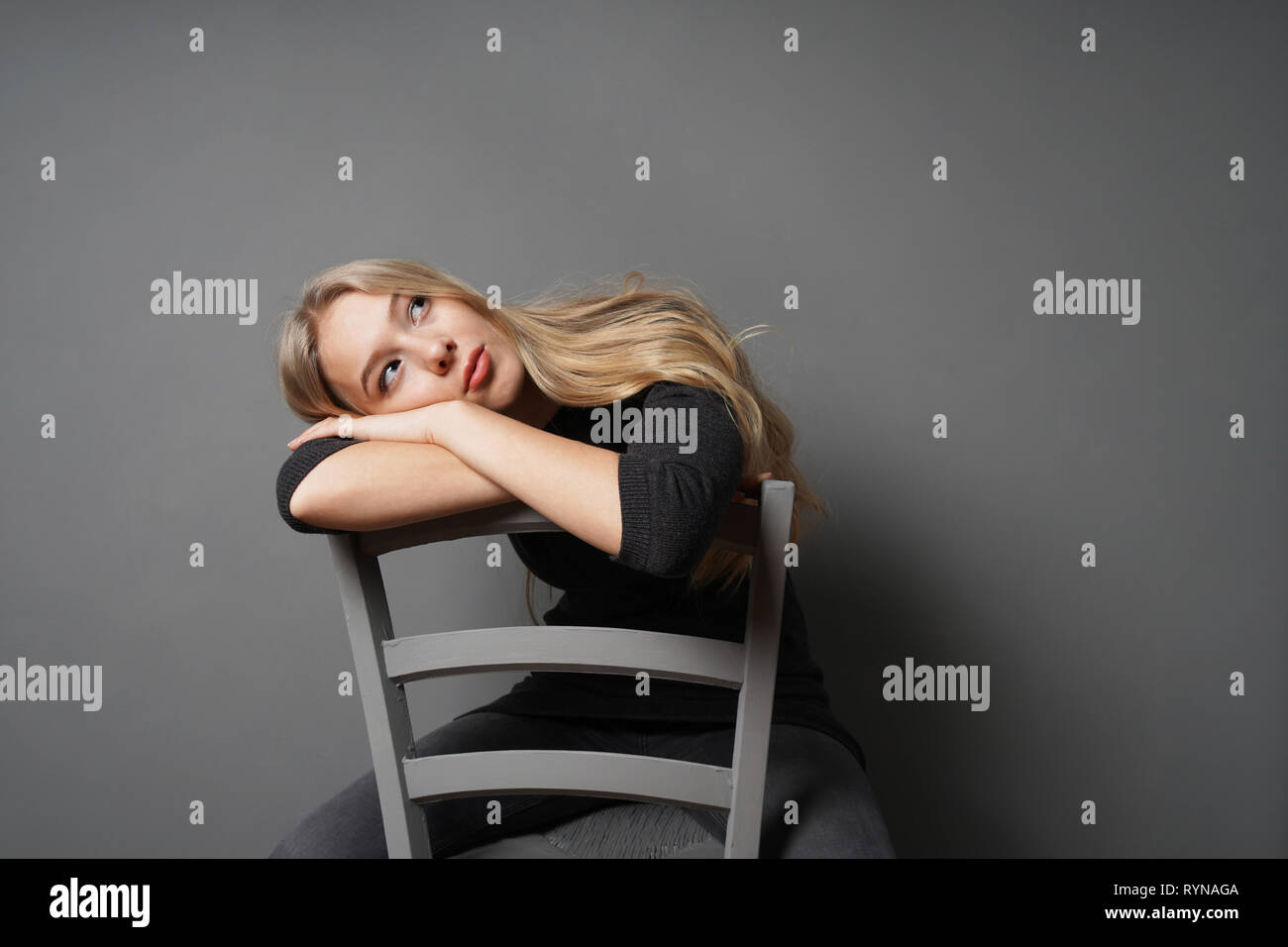 bored female sitting astride on chair and staring at ceiling - gray background with copy space - Stock Image