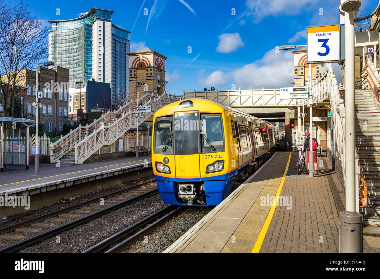 A London Overground train heading for Clapham Junction pulls into West Brompton station with the Empress State Building in the distance - Stock Image