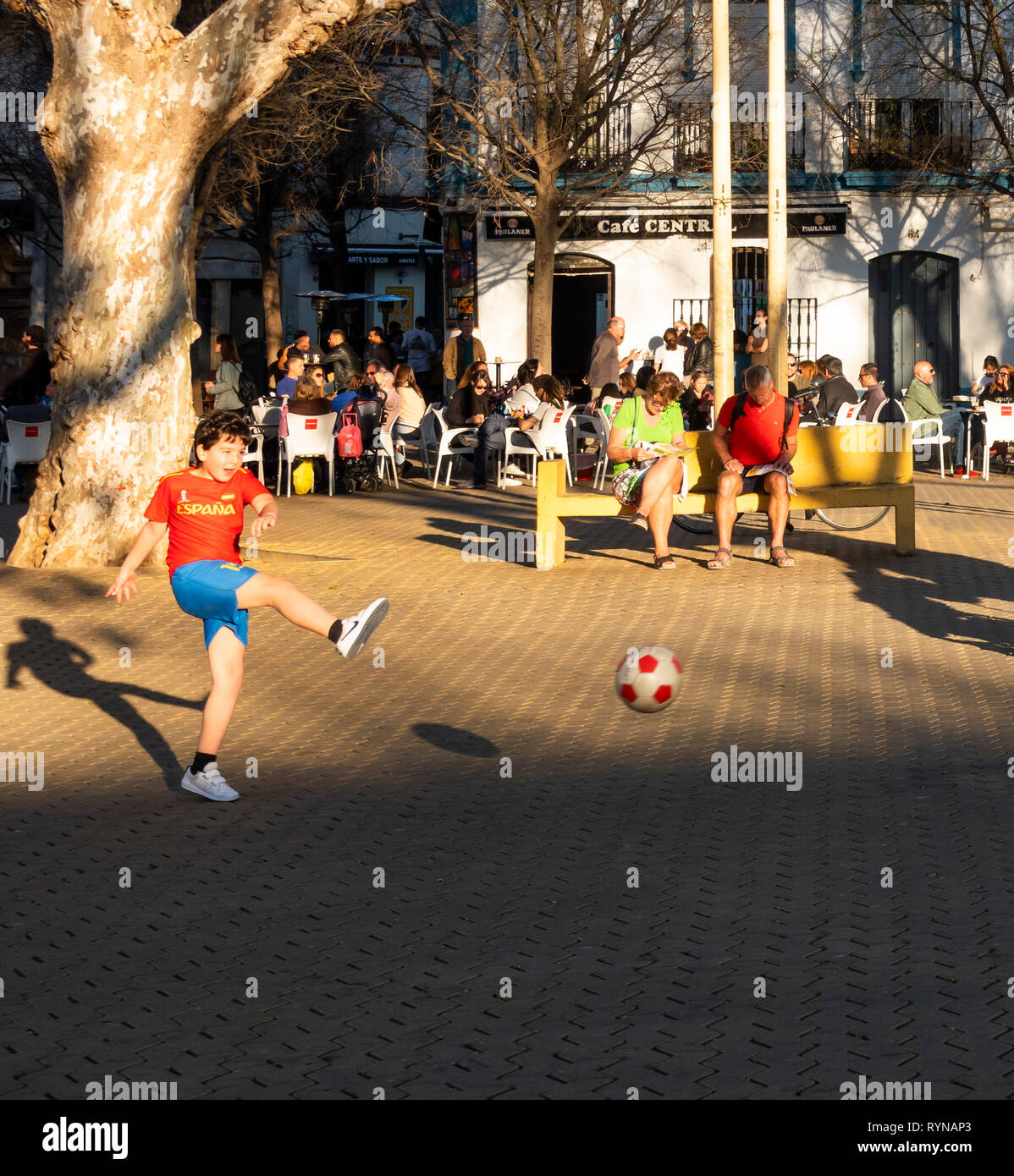A young boy kicking a soccer ball in the Alameda de Hercules in Seville - Stock Image