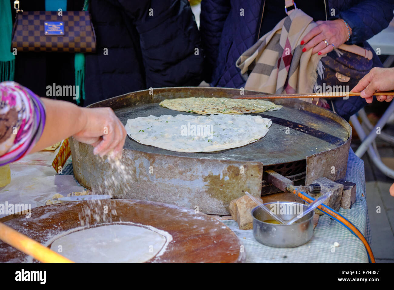 Local woman preparing turkish pancakes (gozleme) . Focus on hot plate and method in Antalya, Turkey - December 29, 2018 Stock Photo