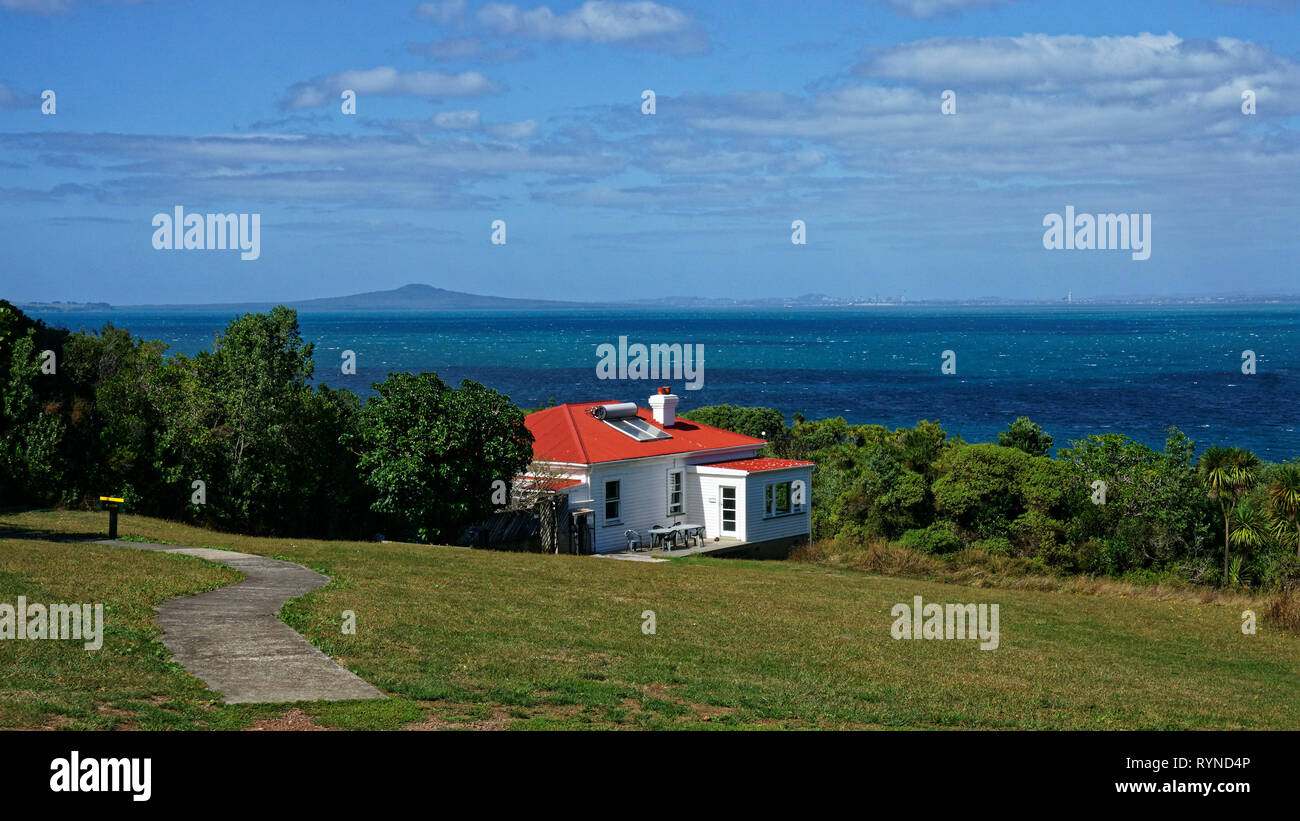 Accommodation bunkhouse on Tiritiri Matangi Island open nature reserve, New Zealand. Volcano Rangitoto in the background. - Stock Image