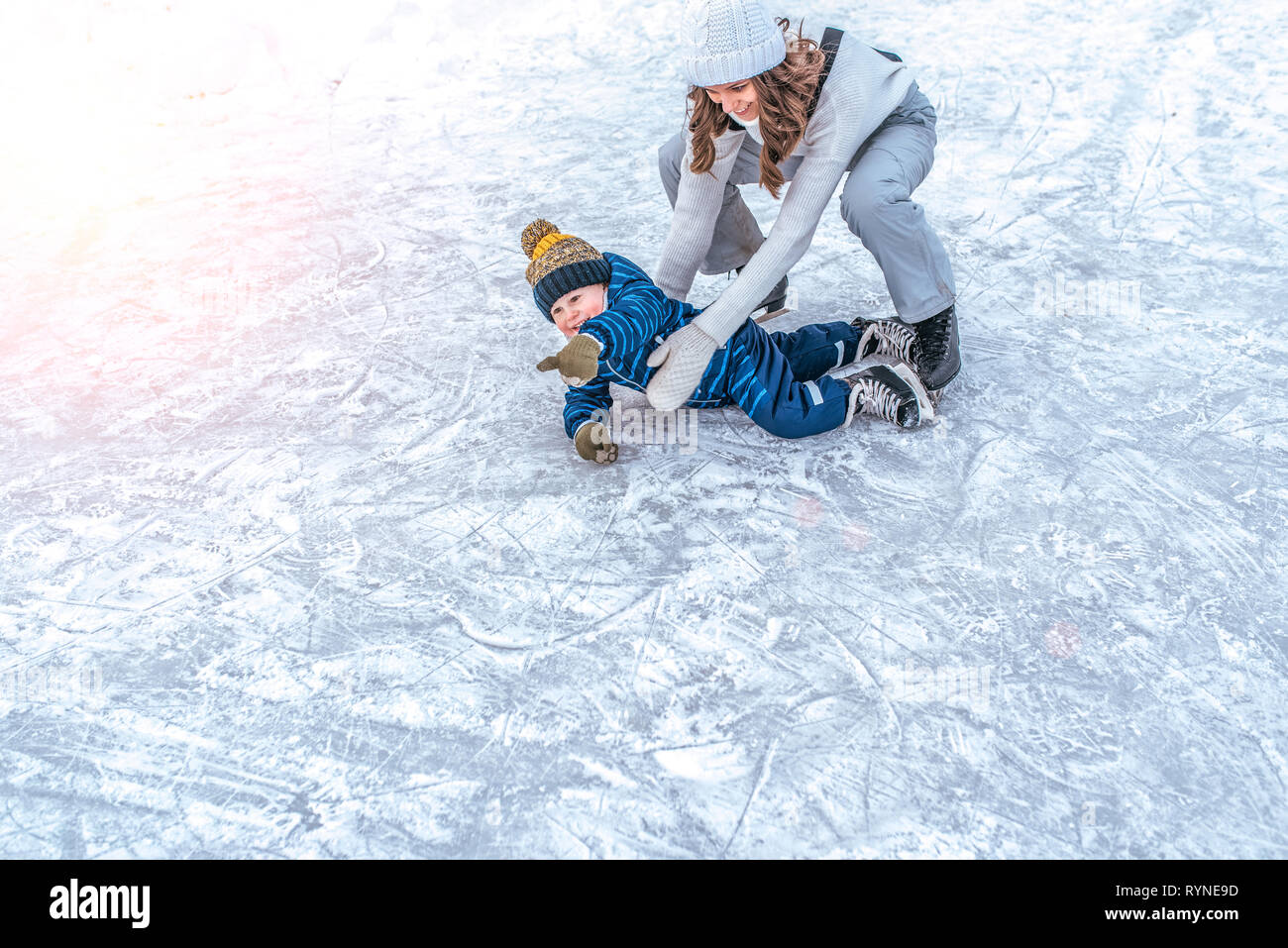 The baby fell on the ice. A young mother skates in the park in winter, with her son a young child 3-5 years old. Weekend rest at a public skating rink - Stock Image