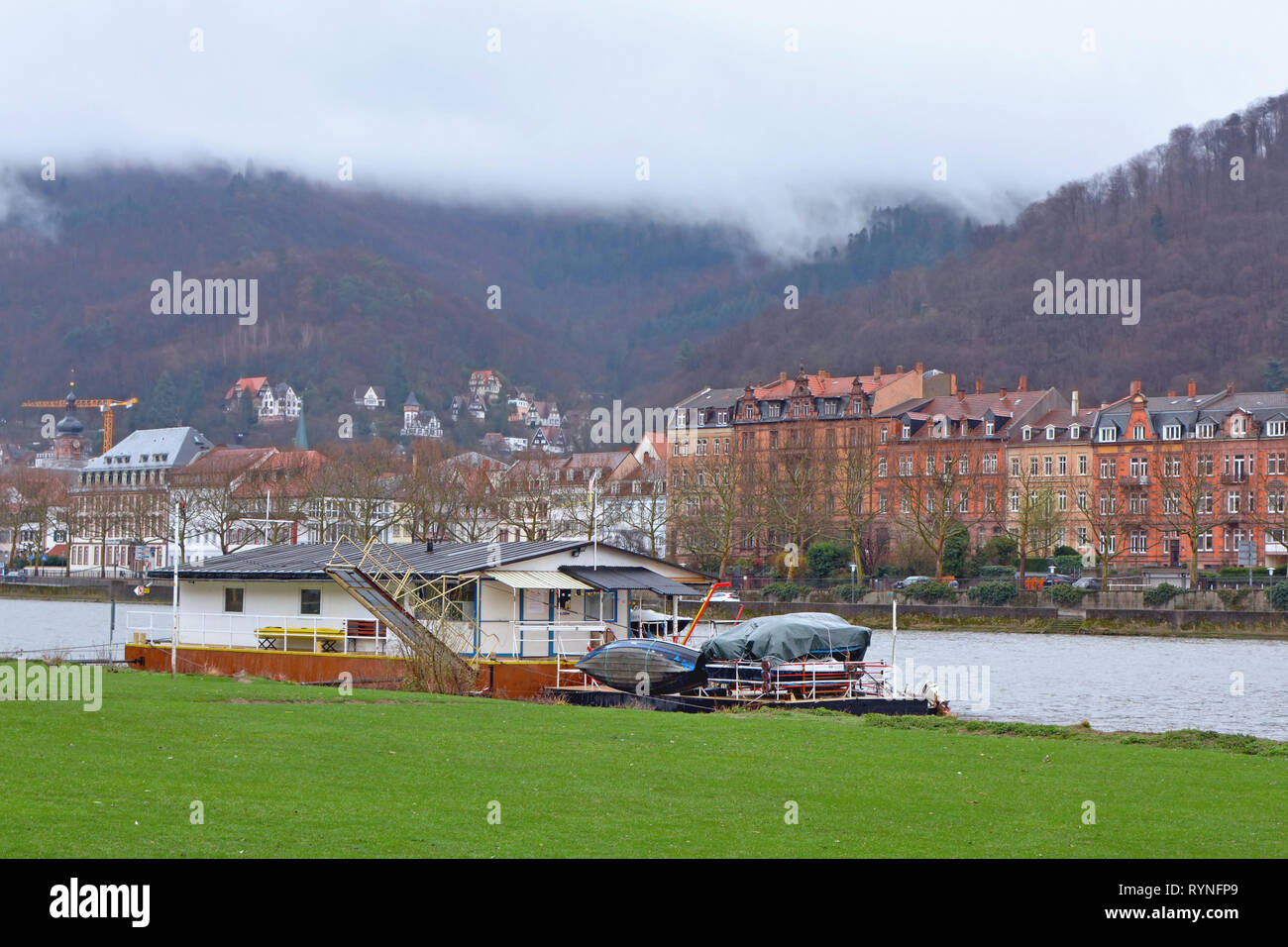 Boat anchored at the Neckar river meadow near city center of Heidelberg, with old buildings and beautiful hill landscape with mist raising in Germany - Stock Image