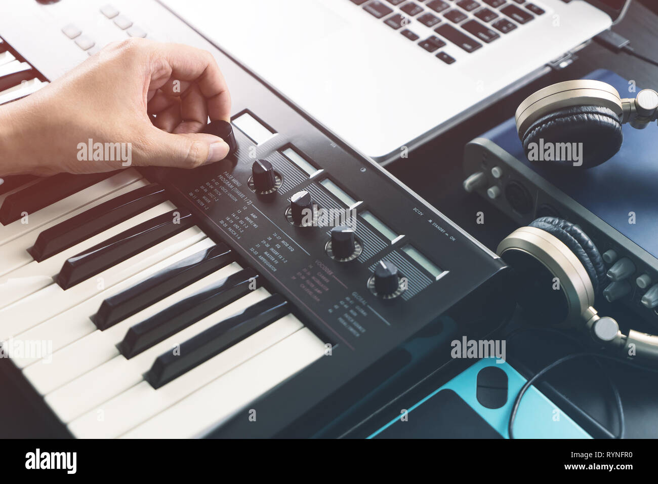 Musician is adjusting sound on synthesizer keyboard - Stock Image