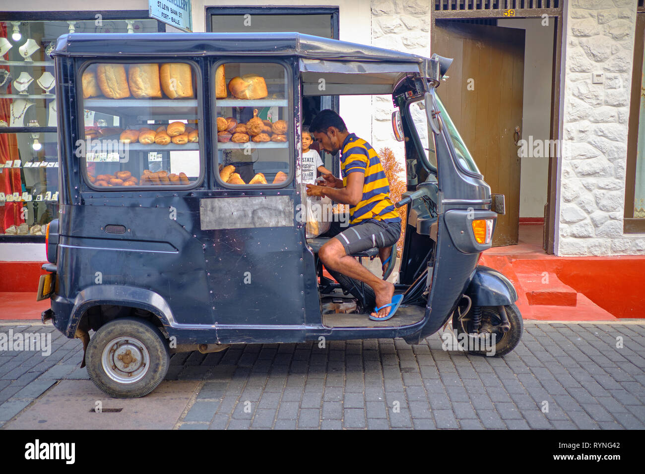 Bread delivery man in black tuktuk in the old part of Galle, under the look of  kid buying . Galle, Sri Lanka, January 9 2018 Stock Photo