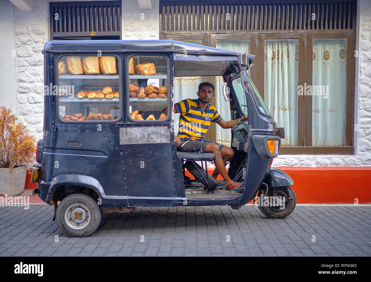 Bread delivery man in black tuktuk in the old part of Galle . Galle, Sri Lanka, January 9 2018 Stock Photo