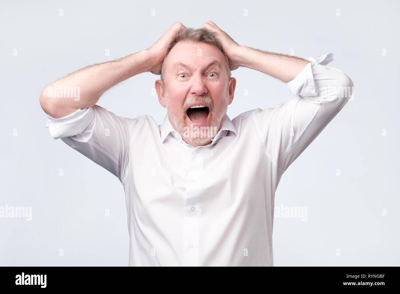 Senior angry man with hand at head on studio wall - Stock Image