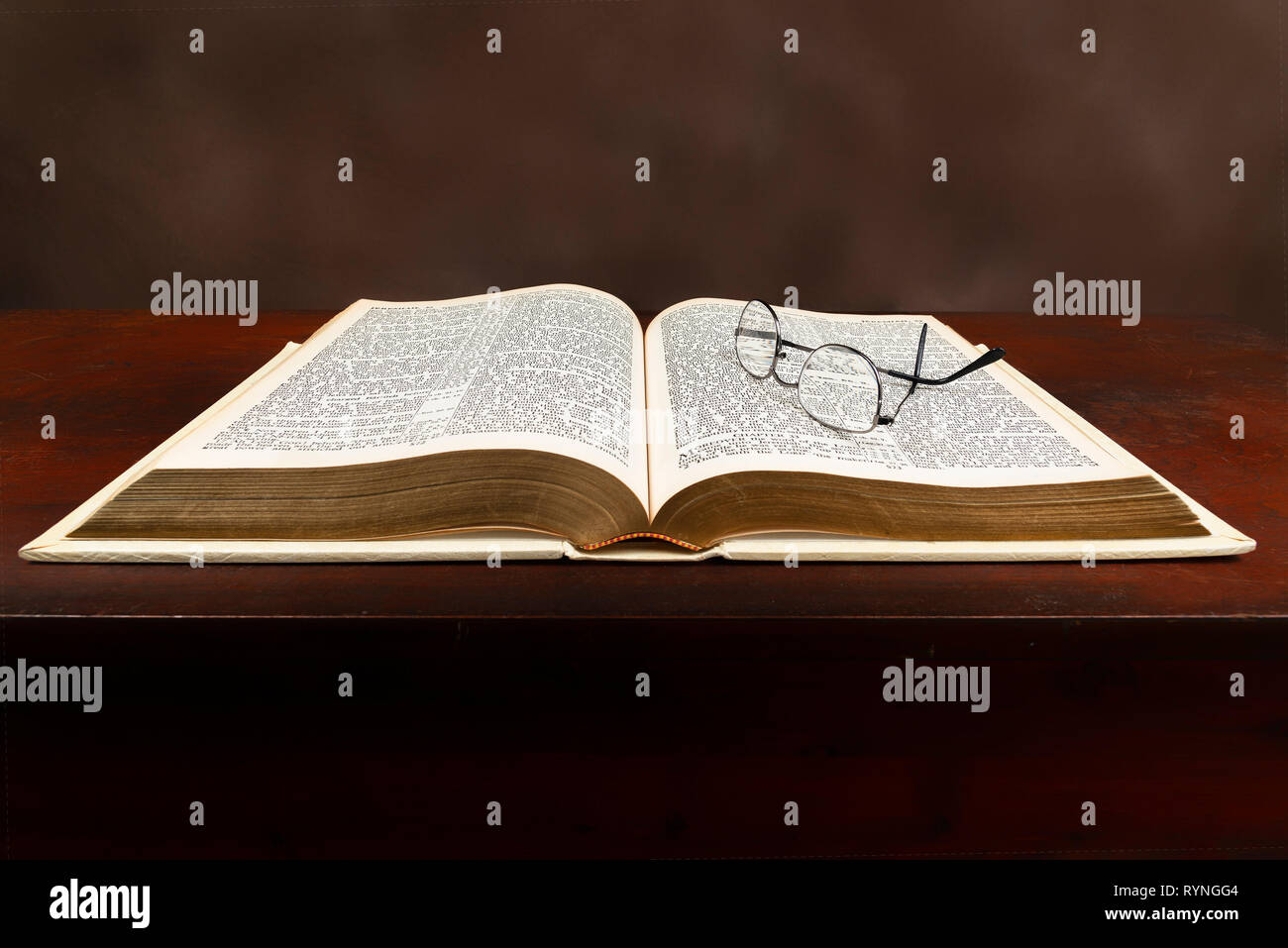 Horizontal close-up shot of an old Bible lying open on a brown background. - Stock Image