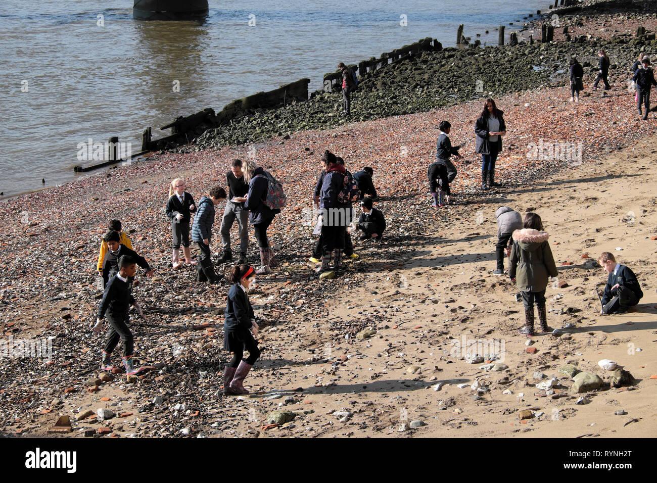 A view of schoolchildren school group mudlarking on the north sandy beach side of the River Thames in winter sunshine London England UK  KATHY DEWITT - Stock Image
