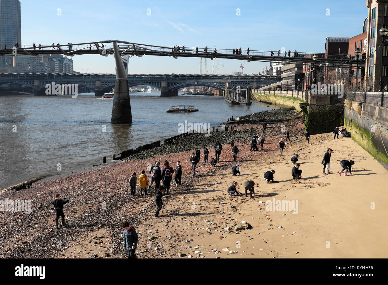 View of schoolchildren archaeology school group at low tide looking for artefacts on the foreshore of the River Thames London England UK  KATHY DEWITT Stock Photo
