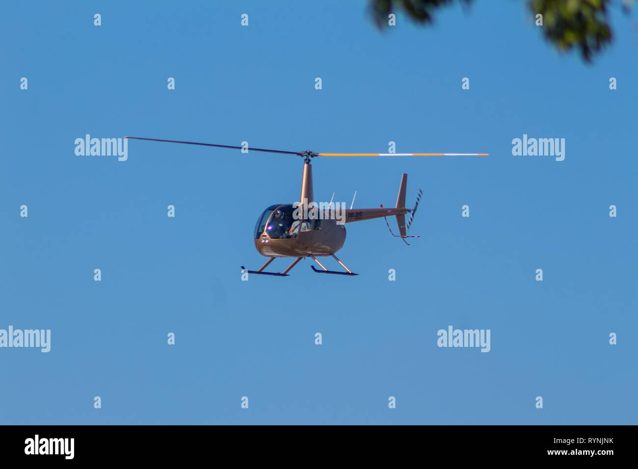 R44 flying low over Autódromo de Interlagos, in São Paulo. - Stock Image