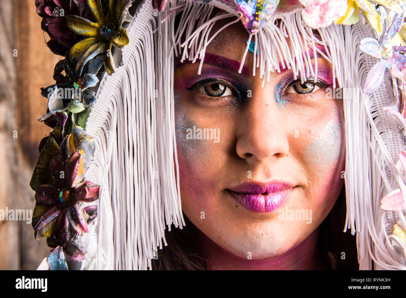 A 25 year old model weating a hat and face paint. - Stock Image
