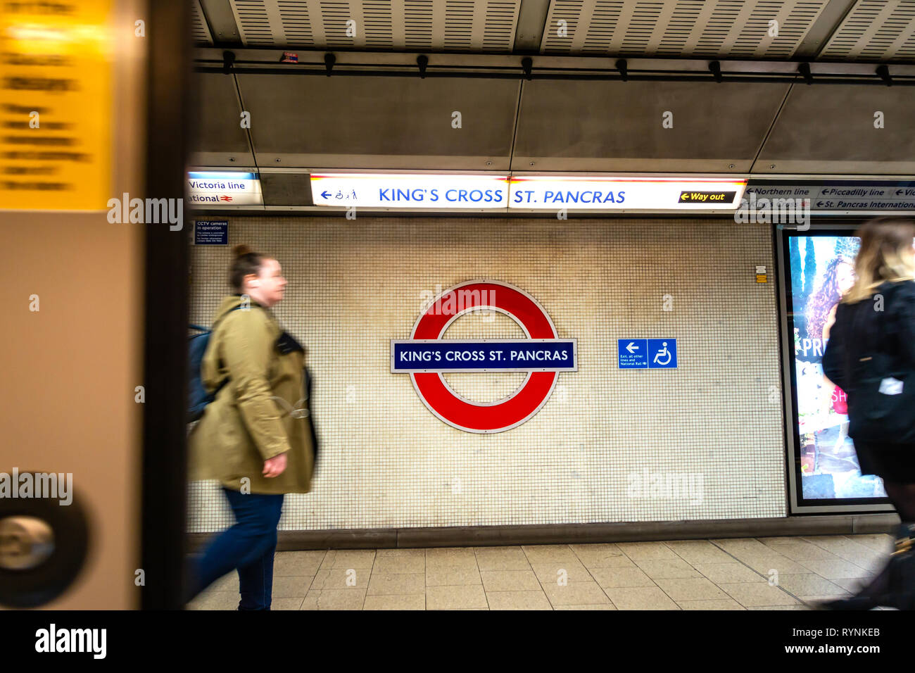 wide angle photograph of people on the platform and Iconic circular Tube sign on the Kings Cross, St Pancras underground platform - Stock Image