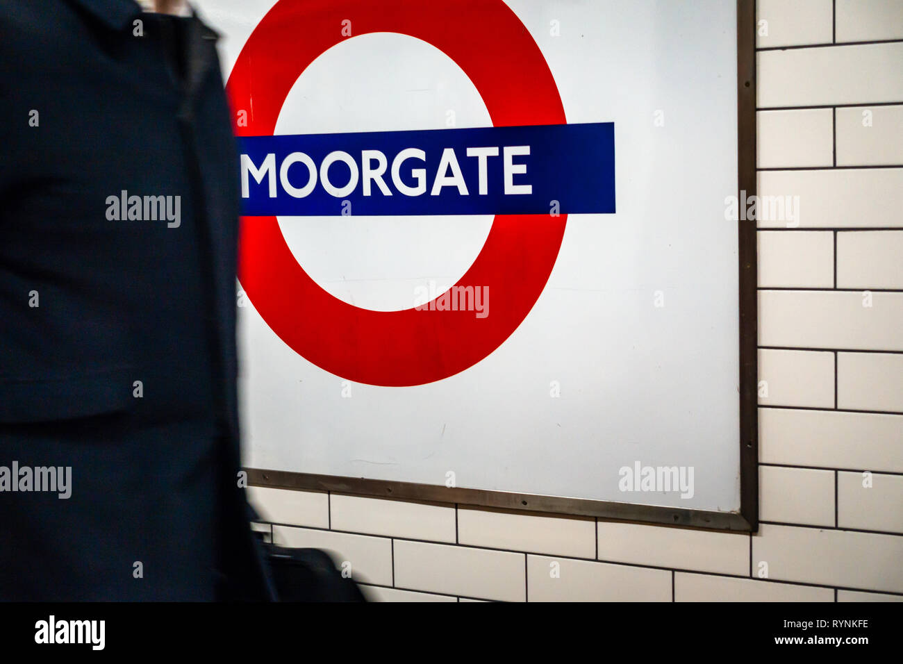 Commuter waking pass the Iconic circular London Tube sign on the underground platform at Moorgate, London - Stock Image
