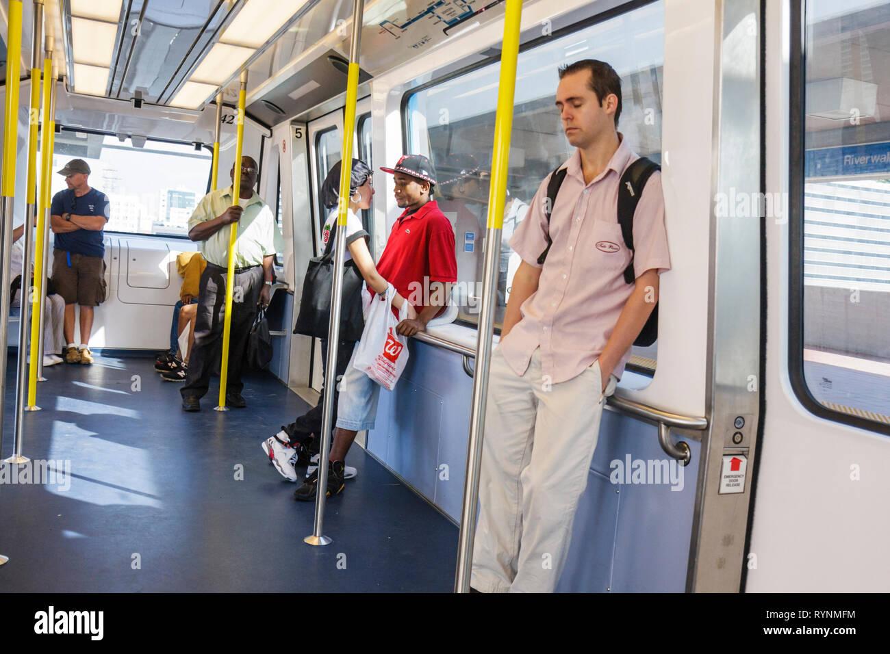 Miami Florida Metromover mass transit public transportation automated people mover Bombardier CX-100 Black woman man men biracia - Stock Image