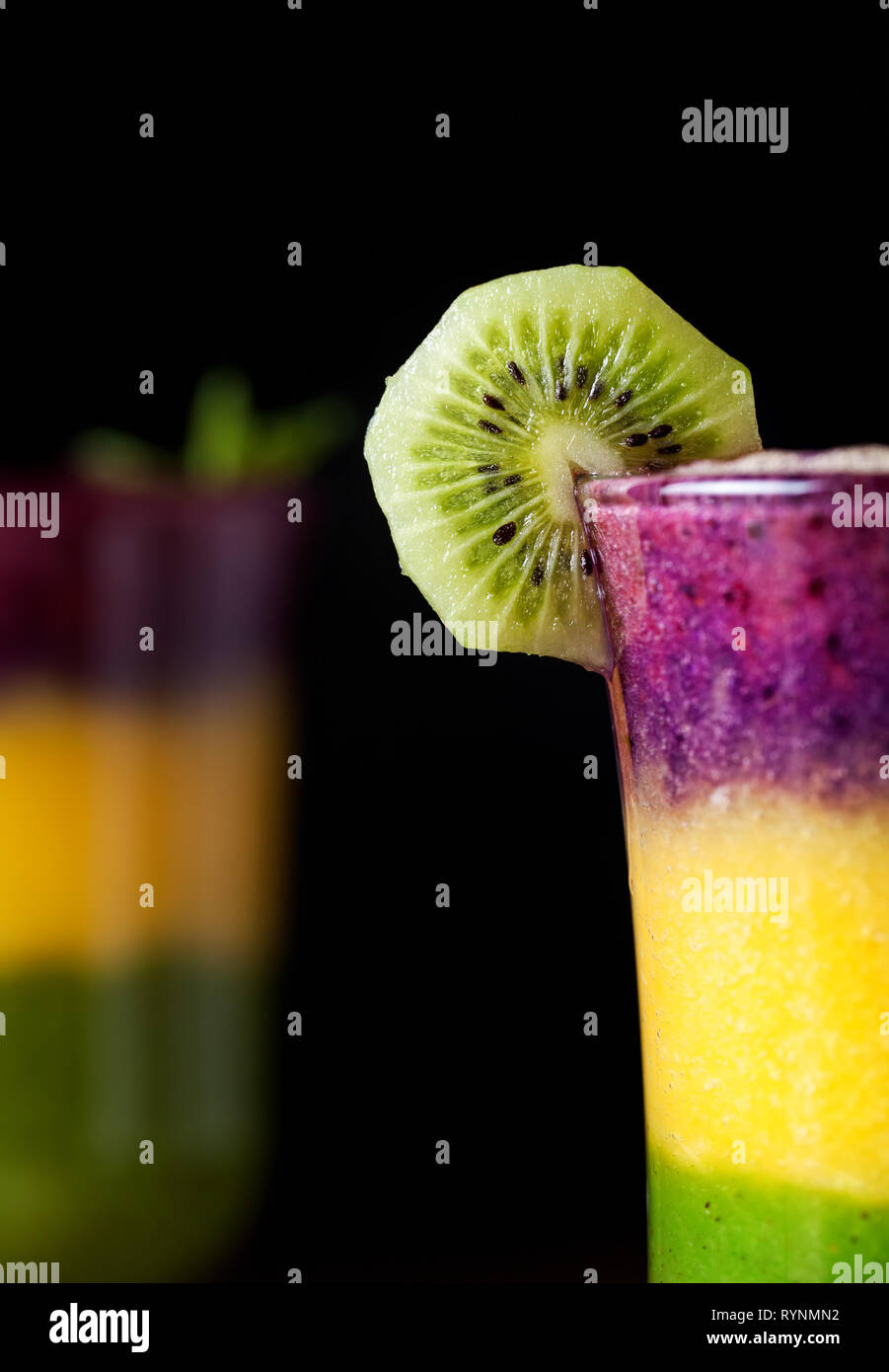 Two glass of smoothie with colorful layers from kiwi, oranges and blackberry on black background close up - Stock Image