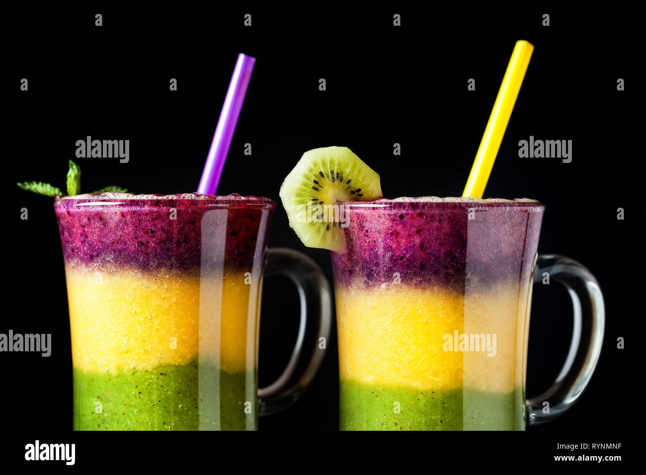 Two glass of smoothie with colorful layers from kiwi, oranges and blackberry on black background close up Stock Photo