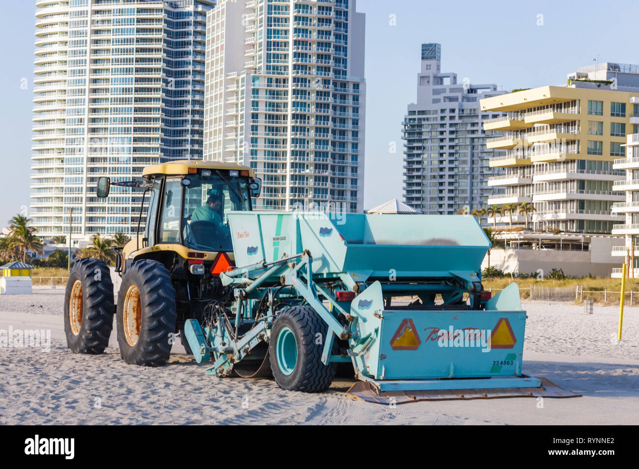 Miami Beach Florida South Beach Atlantic Ocean public beach cleaning cleaner tractor pulling machine sift sand litter city emplo - Stock Image