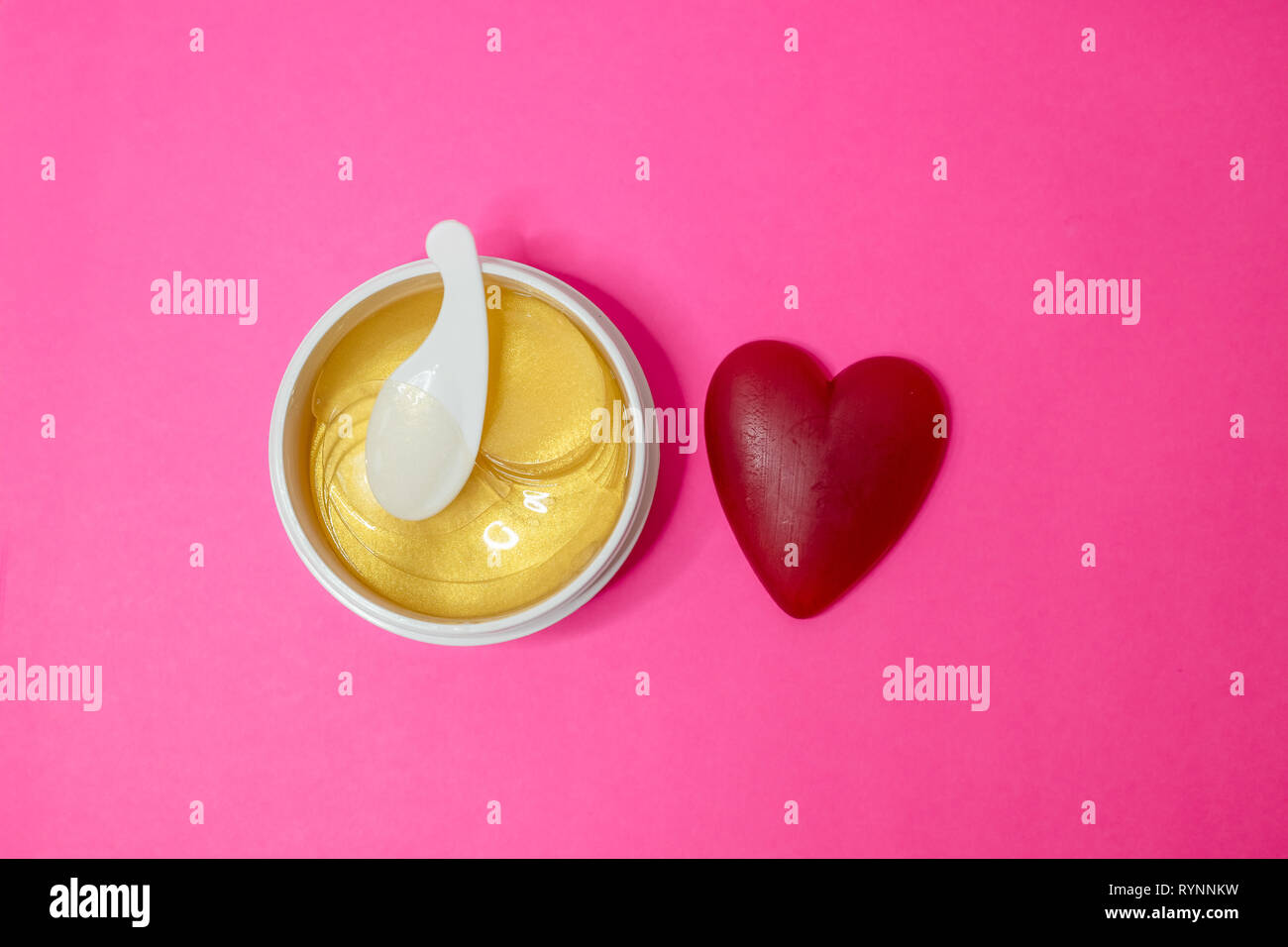 Plastic beauty jar with face mask, container with golden anti aging collagen lifting patches under eyes for woman face care, on pink background - Stock Image