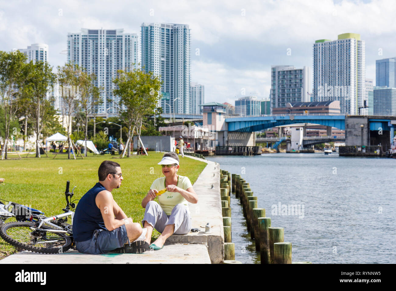 Miami Florida River Bike Miami Days community event Hispanic man woman cyclist bicycle picnic eating leisure older younger - Stock Image
