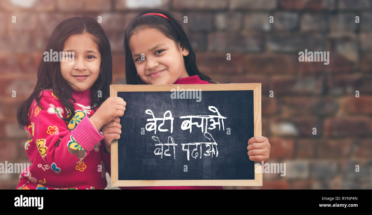 Adorable little 6-8 years old and 8-10 years old Asian girls smiling, holding beti bachao beti padhao chalkboard. Save and educate Daughter concept - Stock Image