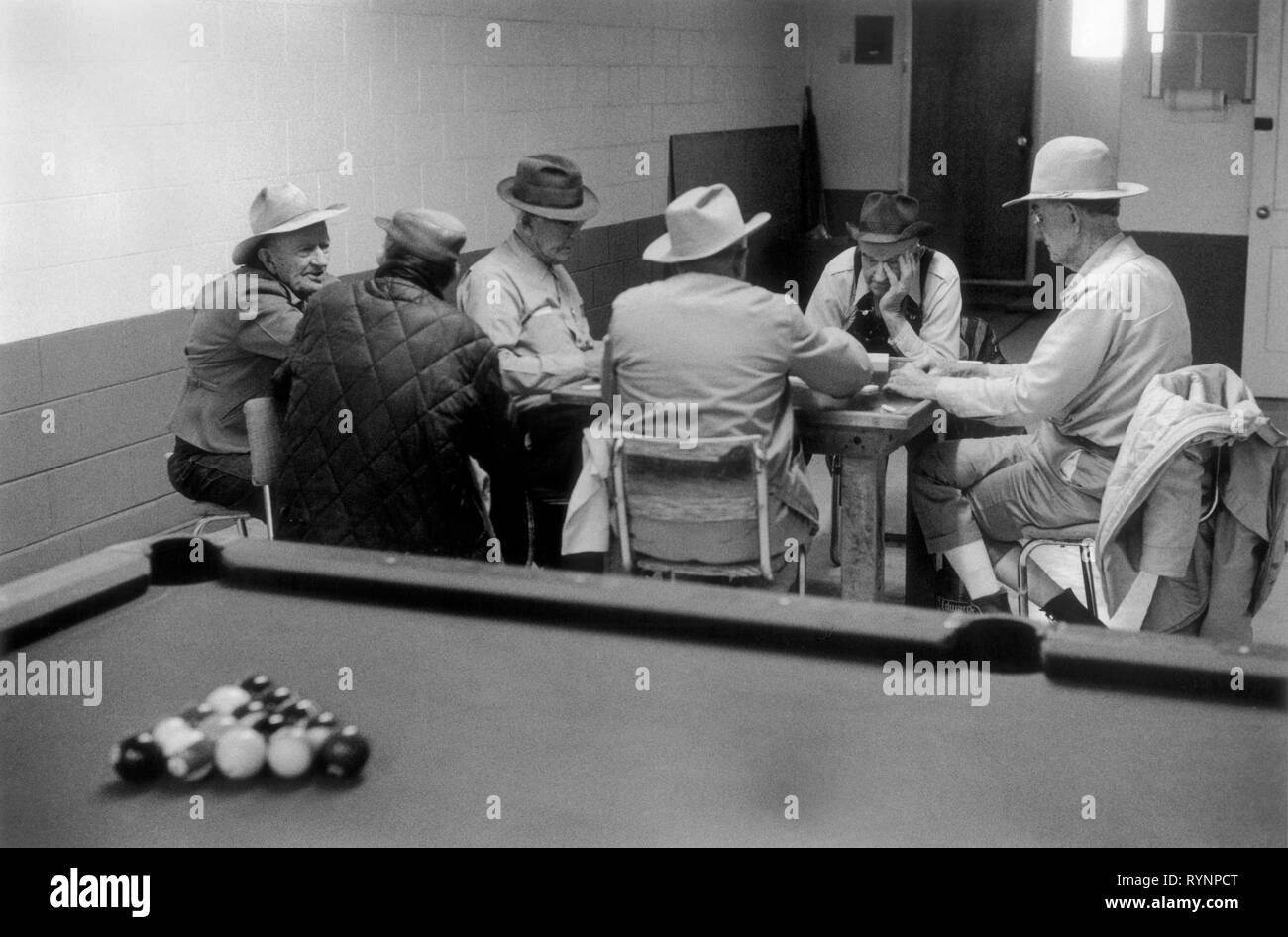AZTEC, NEW MEXICO, USA 1970s: MEN PLAYING DOMINOES IN BAR WITH POOL TABLE.   Six 6 middle old age retired seniors OAP  men male in  pool hall playing dominoes talking passing the time of day concentration wearing cowboy hats candid reportage interior scene . US 70S HOMER SYKES - Stock Image