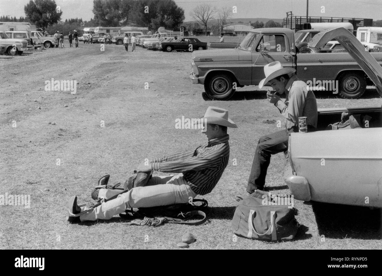 Evanston Wyoming USA 1970s. Two young cowboys, preparing for a rodeo in the car park. One sits on a horse saddle that is on the ground and pretends he is on a horse while another lights a cigarette sitting in the trunk of their automobile. 1971 70s USA US HOMER SYKES - Stock Image