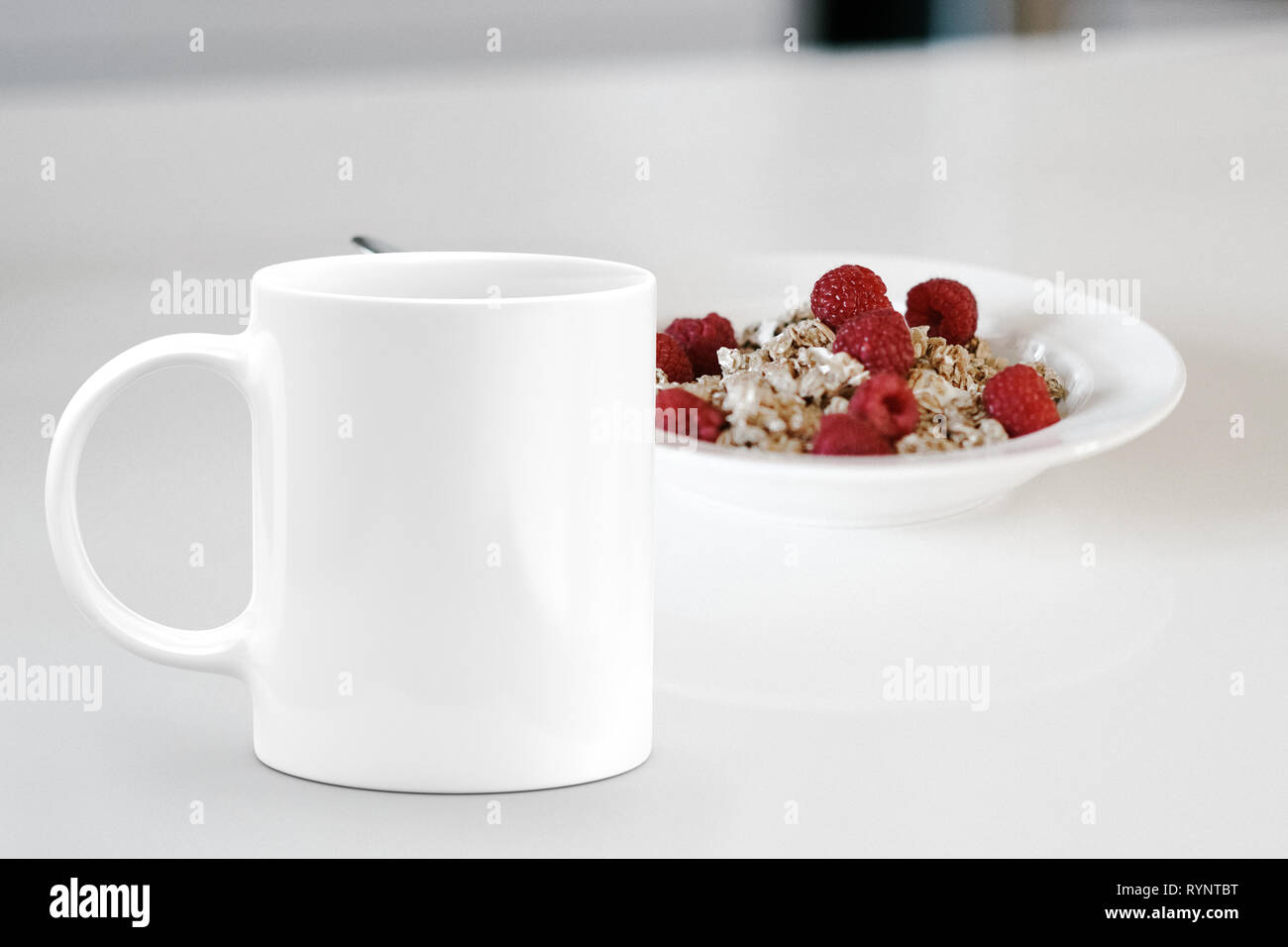 White mug next to a bowl of cereal. Perfect for businesses selling mug mockups Stock Photo