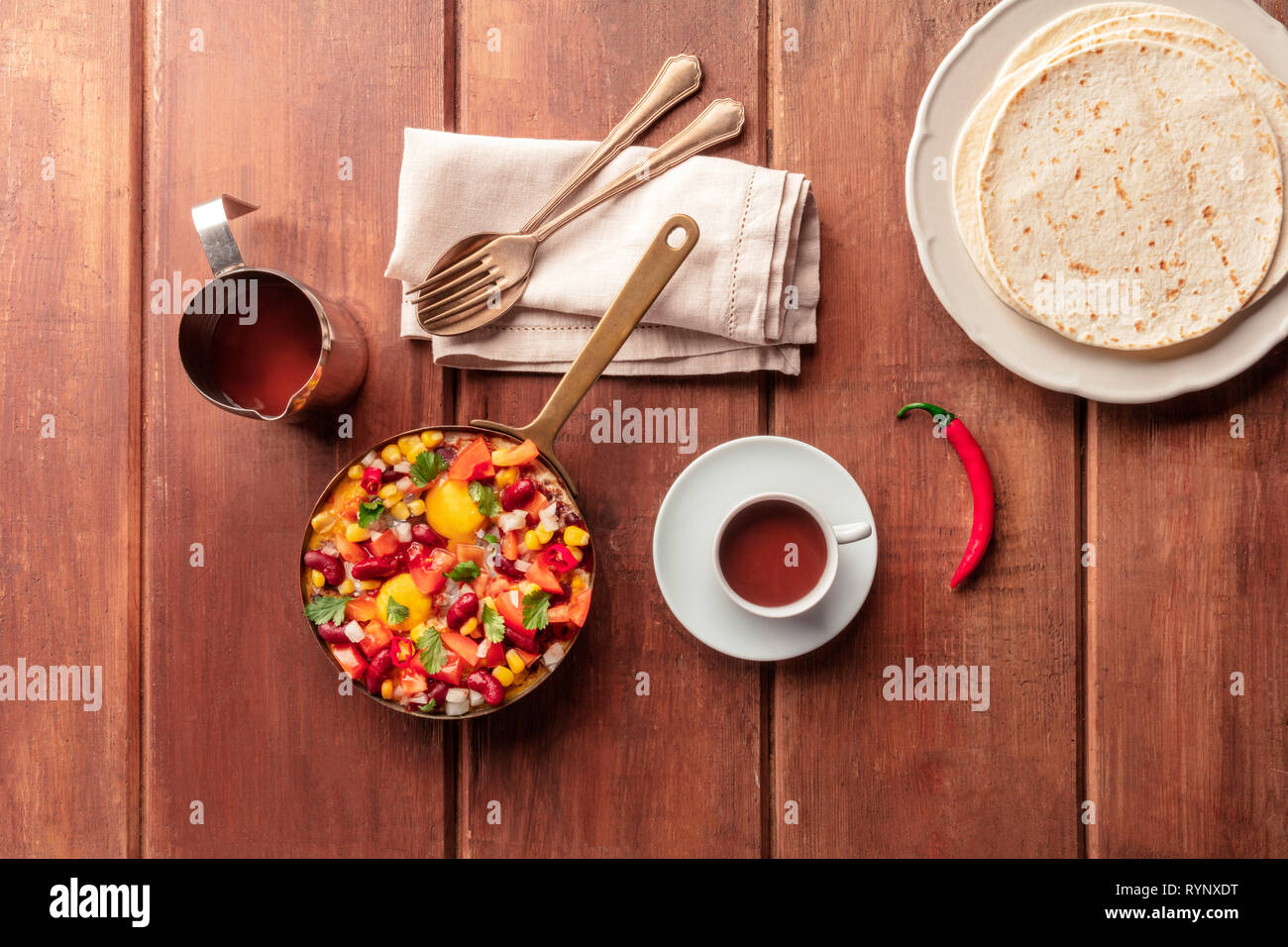 Mexican breakfast. Huevos rancheros, the fried eggs, shot from the top with the pico de gallo salad, hot chocolate, and tortillas - Stock Image