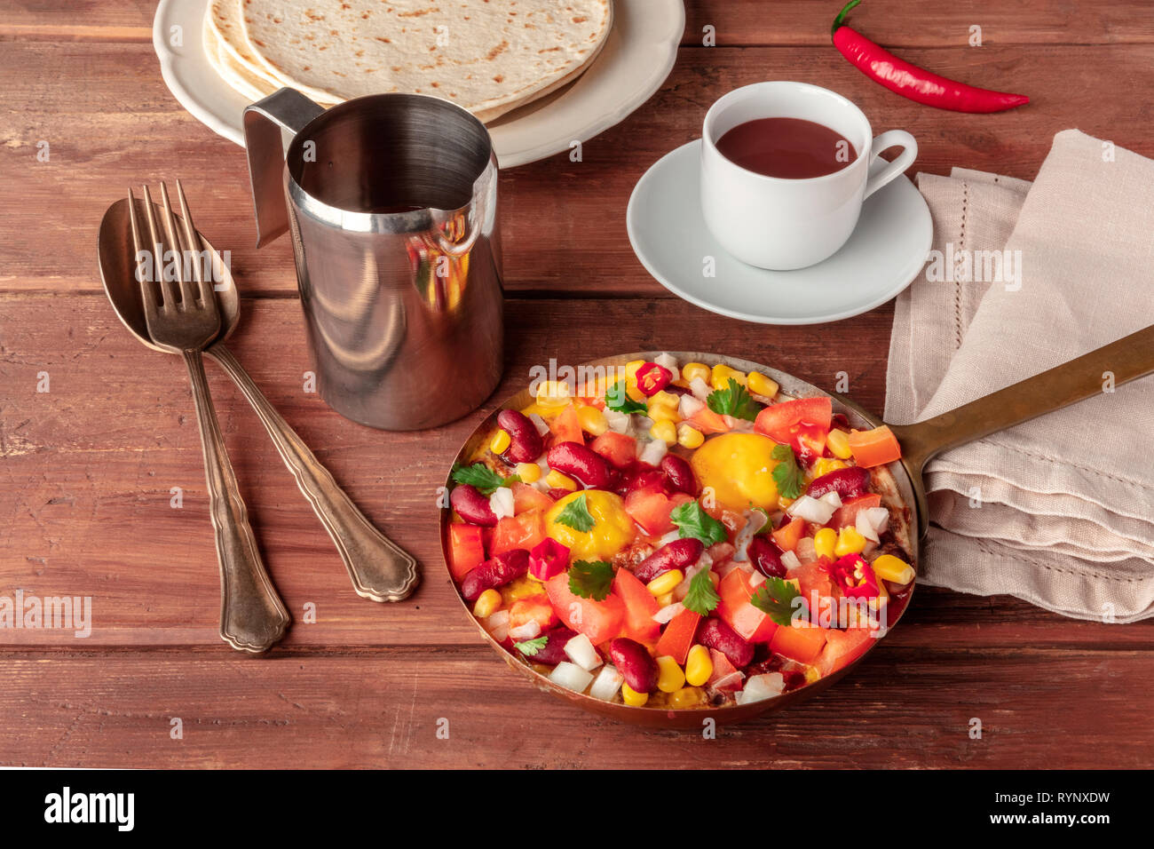 Mexican breakfast. Huevos rancheros, the fried eggs, with the pico de gallo salad, hot chocolate, and tortillas on a dark rustic wooden background - Stock Image