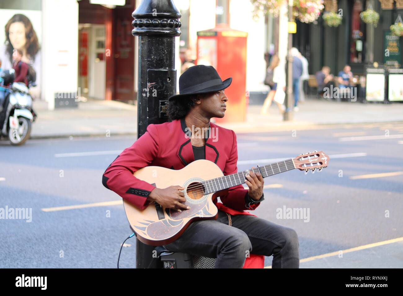 Busker sitting at foot of lamp post playing guitar Stock
