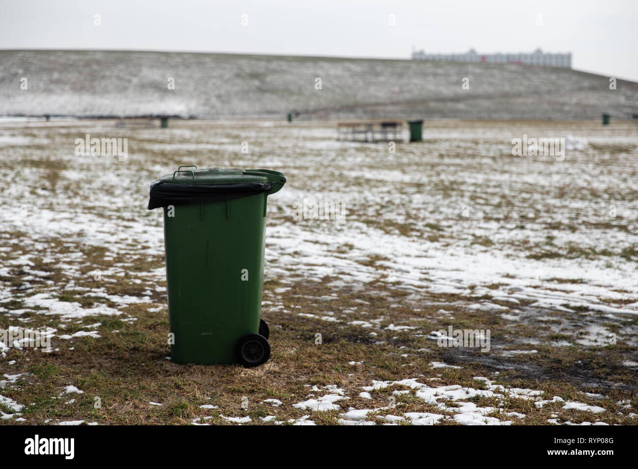 Blank ad space trash can standing in a picnic field in Winter - Stock Image
