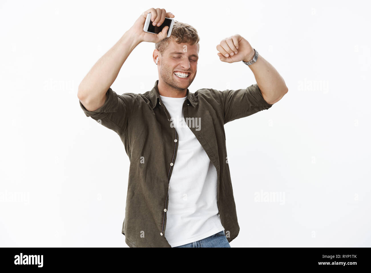 Man feeling happy and awesome dancing from joy with closed eyes and satisfied smile lifting hands holding smartphone wearing wireless earbuds - Stock Image