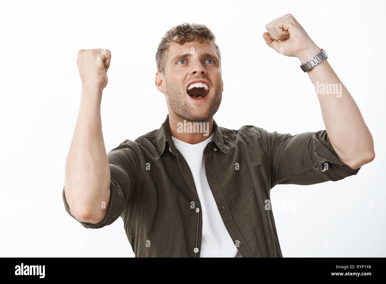 Excited and cheerful handsome man with blue eyes and fair hair looking up at tv screen as cheering having faith in team raising clenched fists in - Stock Image
