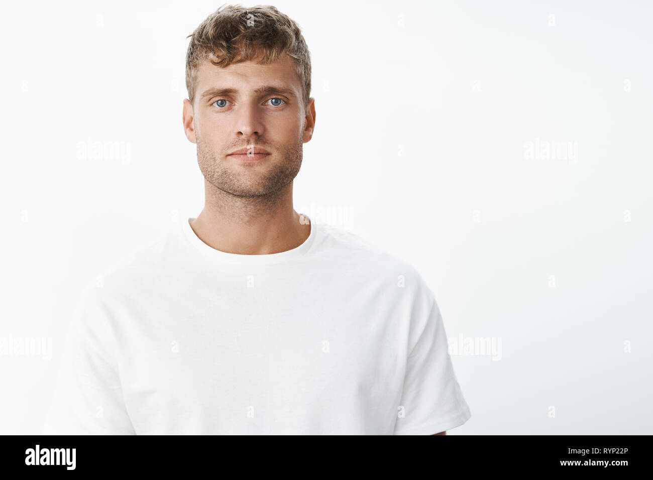 Serious-looking peaceful and calm attractive blond european man with blue eyes and bristle looking at camera focused and chill without emotions - Stock Image